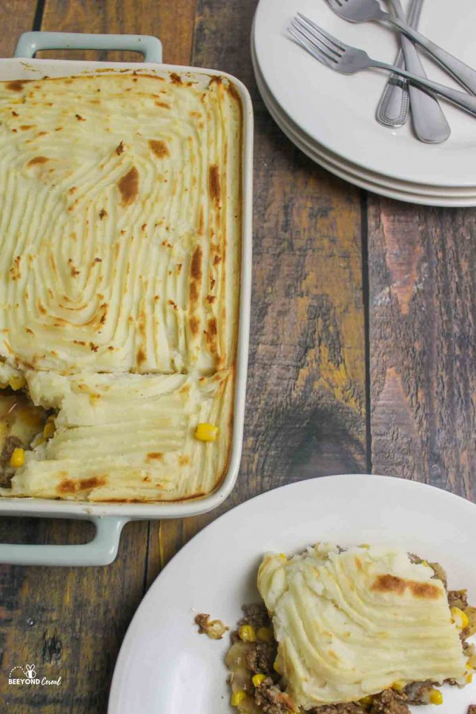 a baking dish full of shepherds pie with a serving removed and empty plates and forks waiting