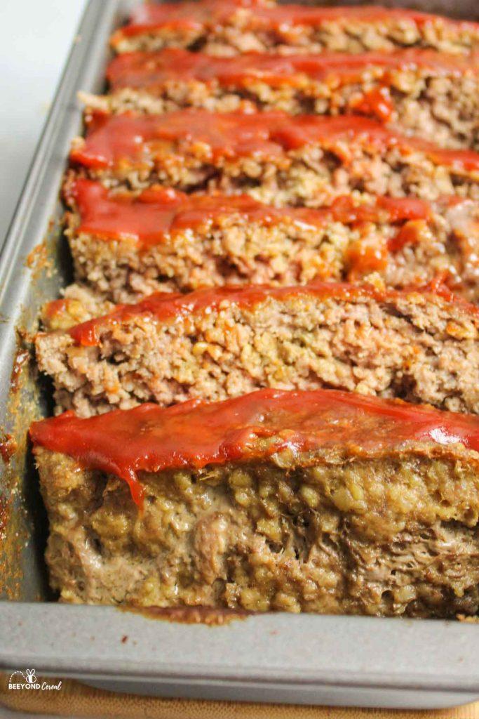 a close up of sliced meatloaf in loaf pan