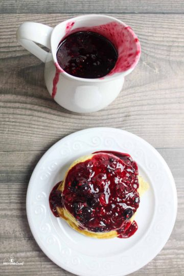 a stack of pancakes covered in berry syrup and in a pitcher