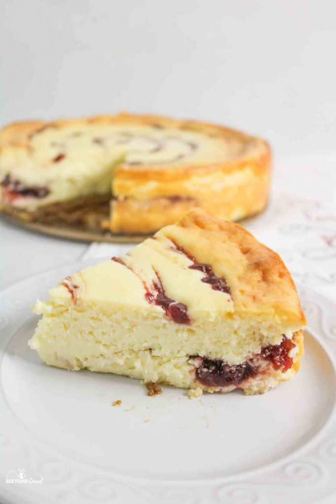 a slice of cranberry white chocolate cheesecake in front of the remaining cheesecake