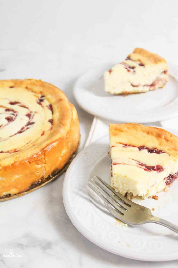 slices of cranberry white chocolate cheesecake on plates
