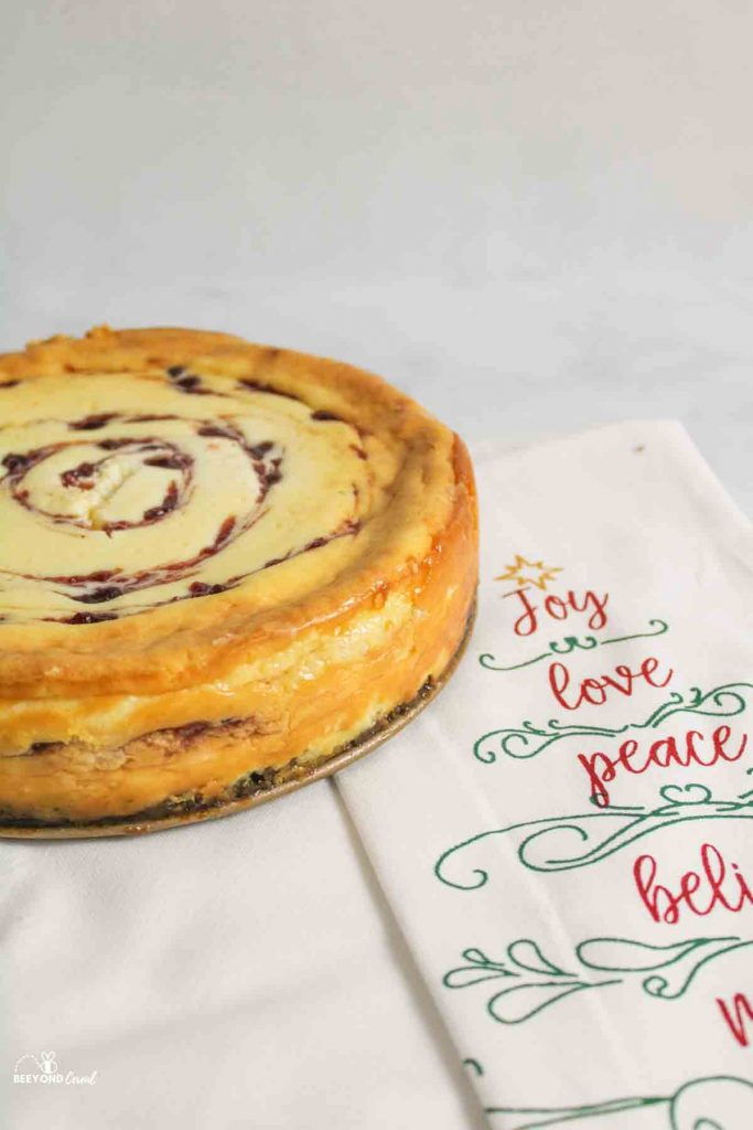 a baked cranberry white chocolate cheesecake next to a tea towel