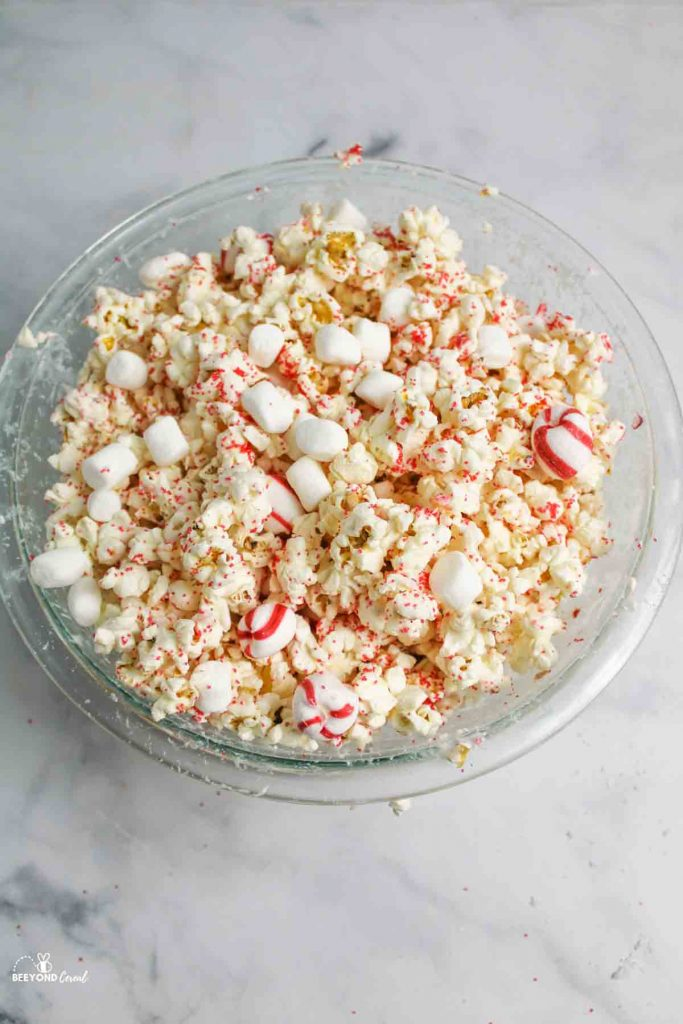 a bowl of peppermint white chocoalte popcorn with scattered popcorn around it