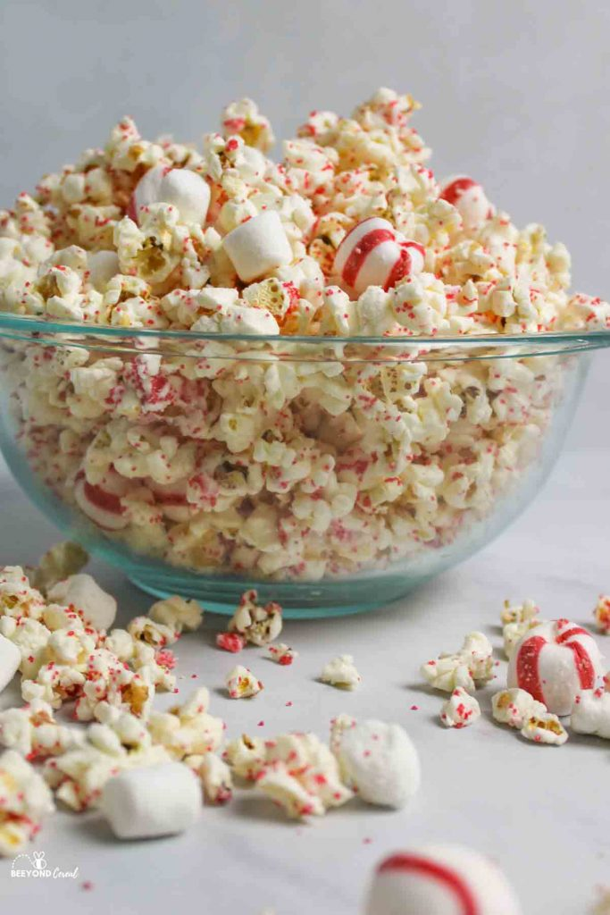 a side view of a glass bowl filled with white chocolate peppermint popcorn and scattered popcorn around it