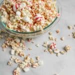 a bowl of white chocolate peppermint popcorn off to the side with scattered candies and popcorn around it