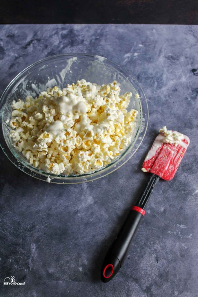 white chocolate covered popcorn in a glass bowl next to used red spatula