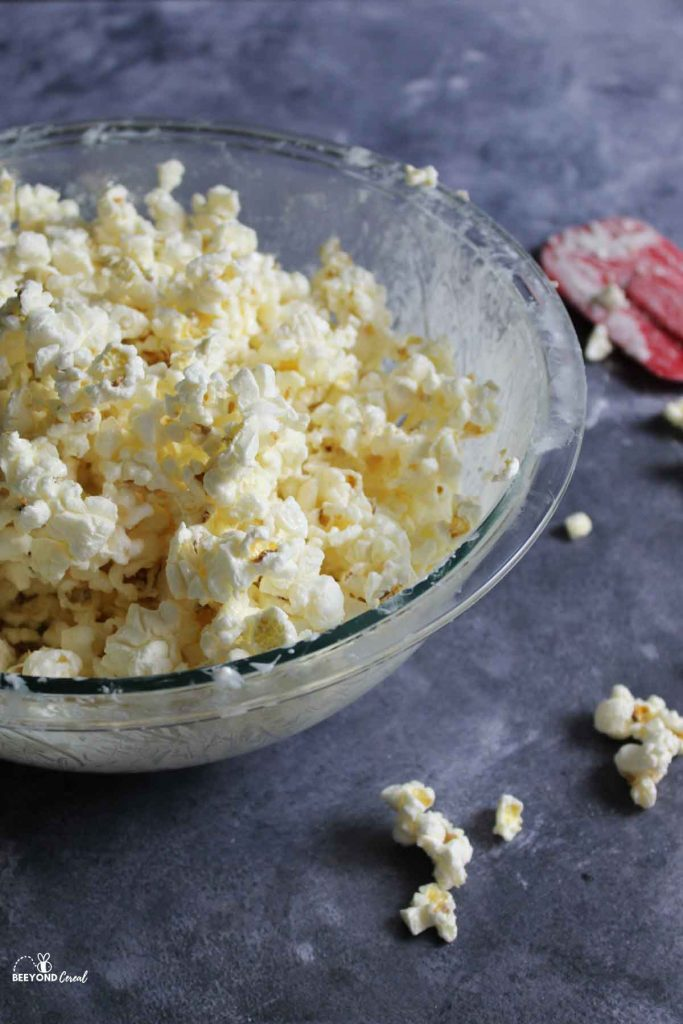a messy glass bowl filled with white chocolate covered popcorn