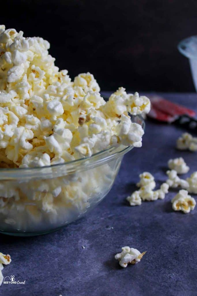 a tall pile of white chocoalte popcorn in a bowl