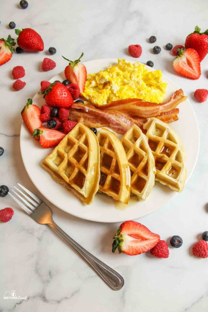 a white plate with scrambled eggs, bacon, fresh berries and syrup topped waffle wedges and a fork and fruit to the sides