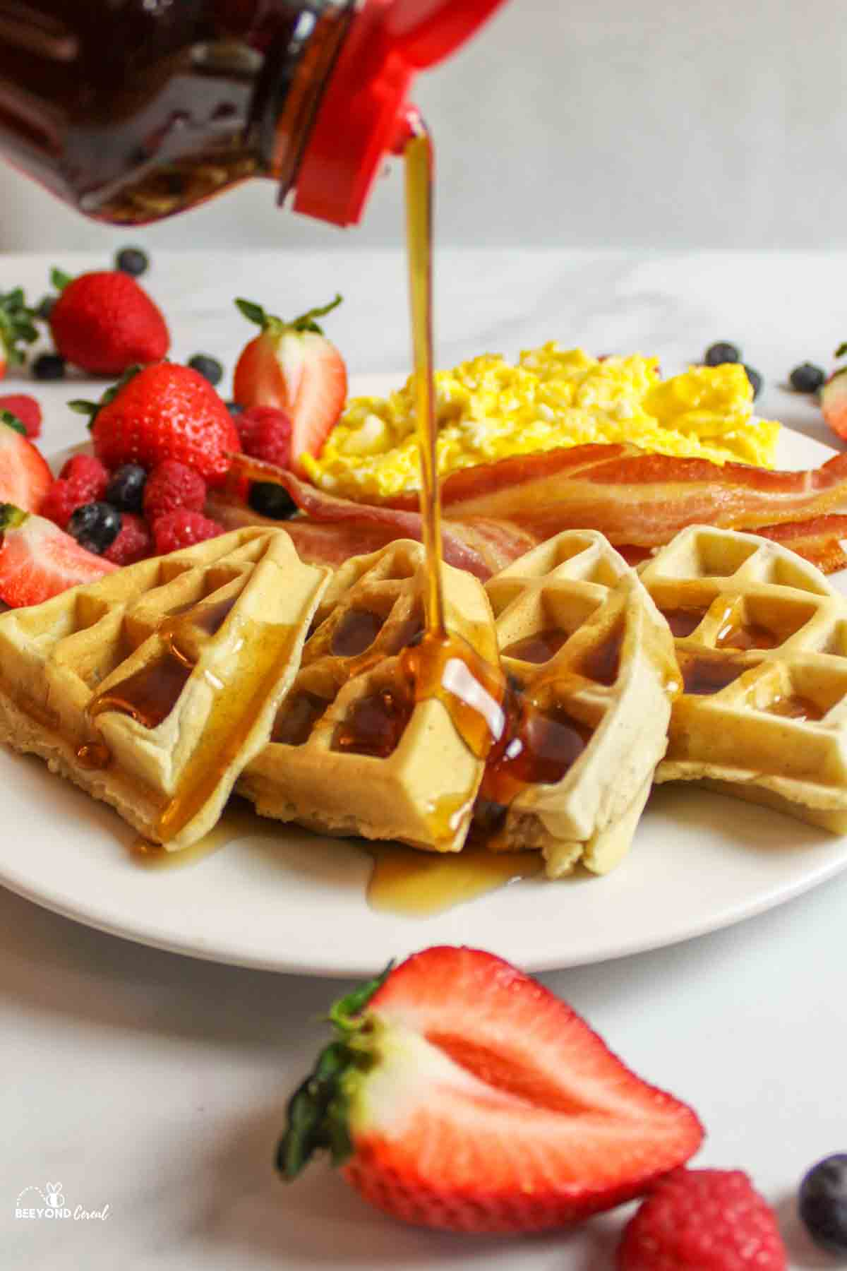 pouring syrup on a waffle with fresh berries all around