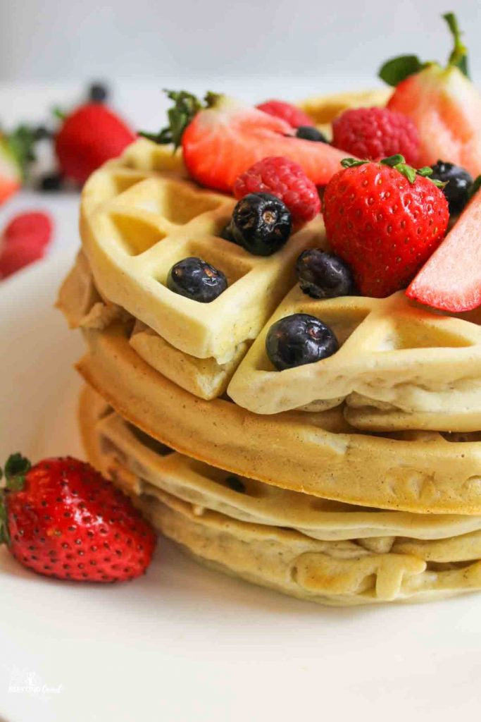 stacked waffles on a white plate with fresh berries on top and to the side and background