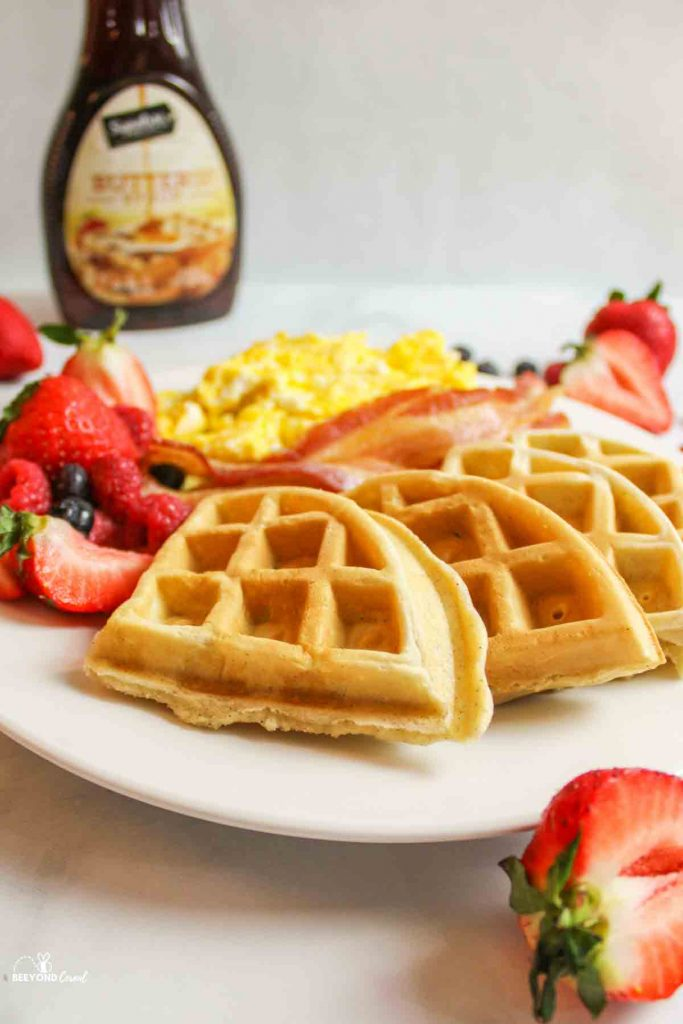 side view of waffle slices on a plate with eggs, bacon and fresh berries and a bottle of syrup in the background