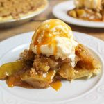 an applepie slice with ice cream scoop on top and drizzle of caramel sauce