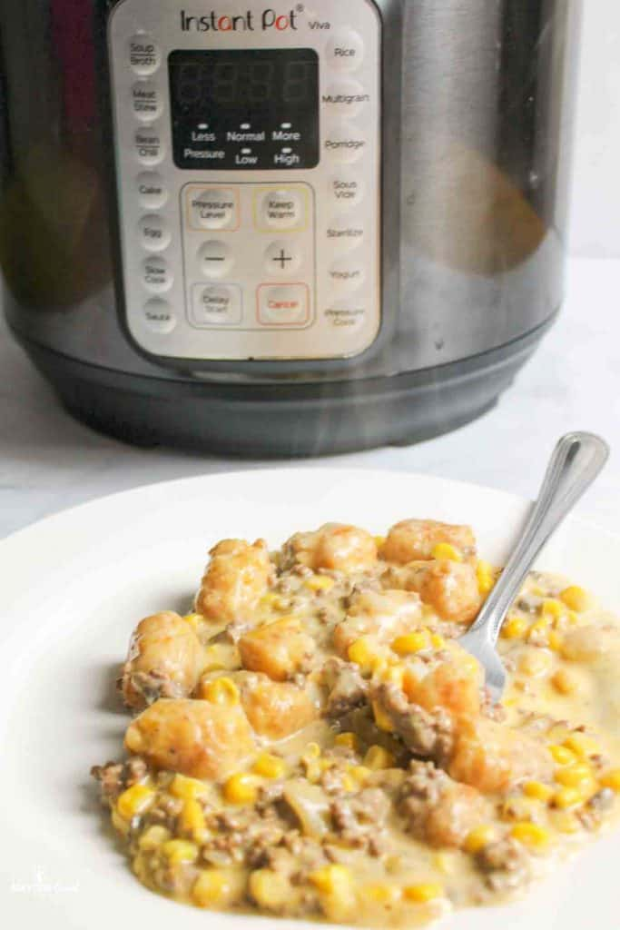 an instant pot behind a plate of tater tot casserole with a fork