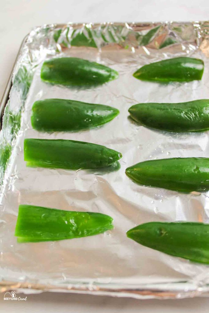 close up of jalapenos on a foil lined baking sheet ready for roasting