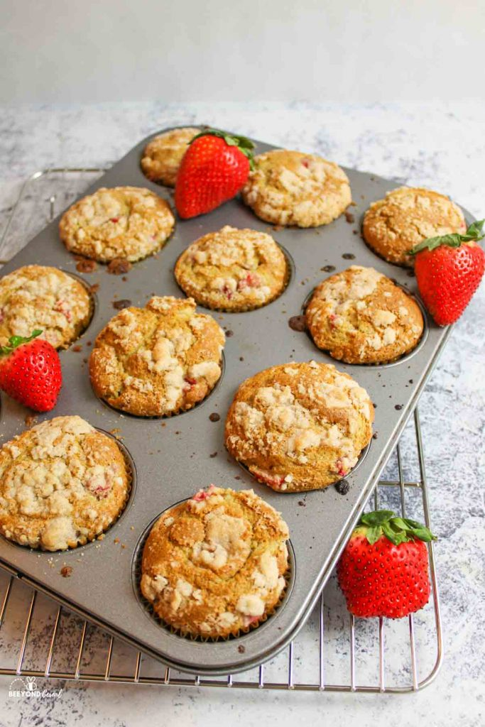 muffins in a muffin tray on a wire rack with fresh strawberries
