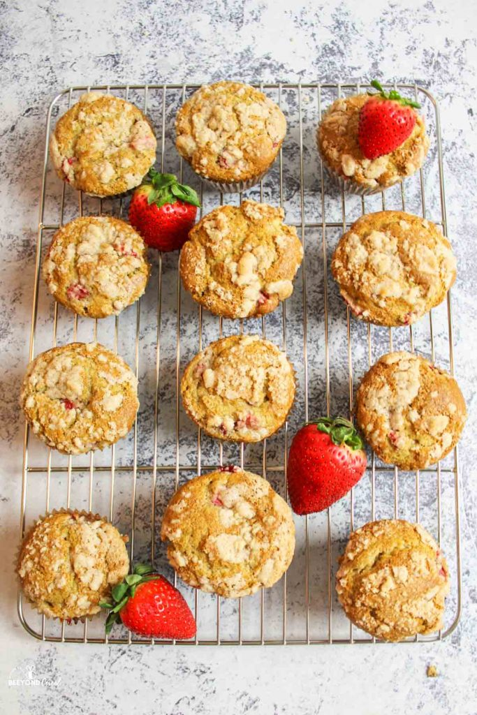 aerial view of muffins on a wire cooling rack with fresh strawberries