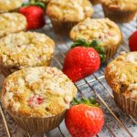 strawberry muffins on a wire rack with fresh strawberries scattered around