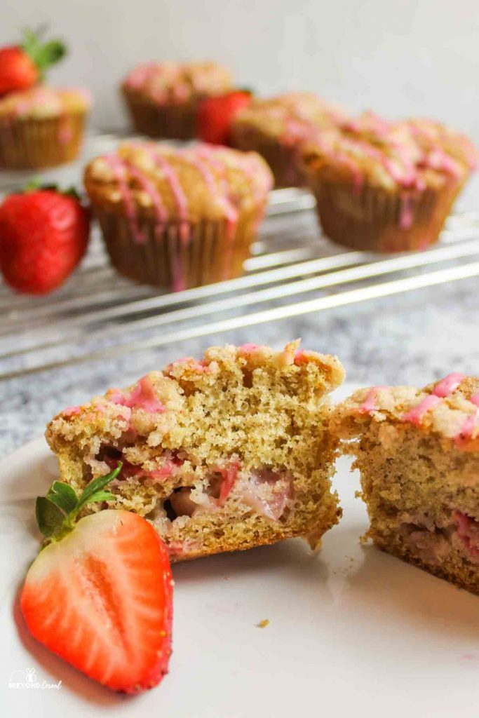 a muffin split open on a plate to reveal cooked strawberries and soft crumb inside