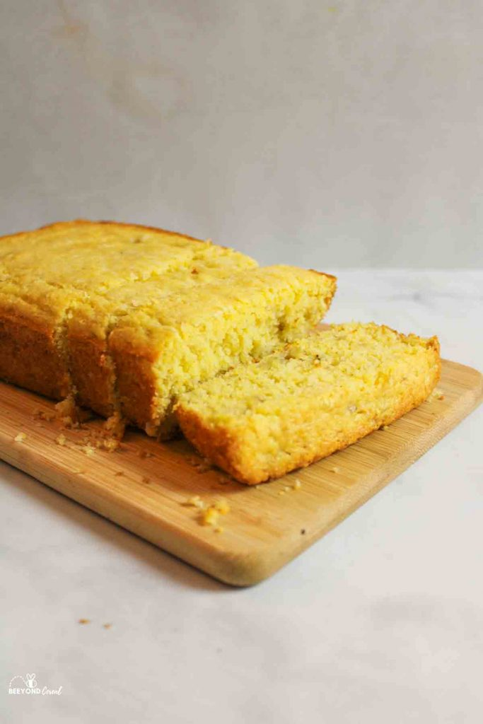 a sliced loaf of banana cornbread on a wooden cutting baord