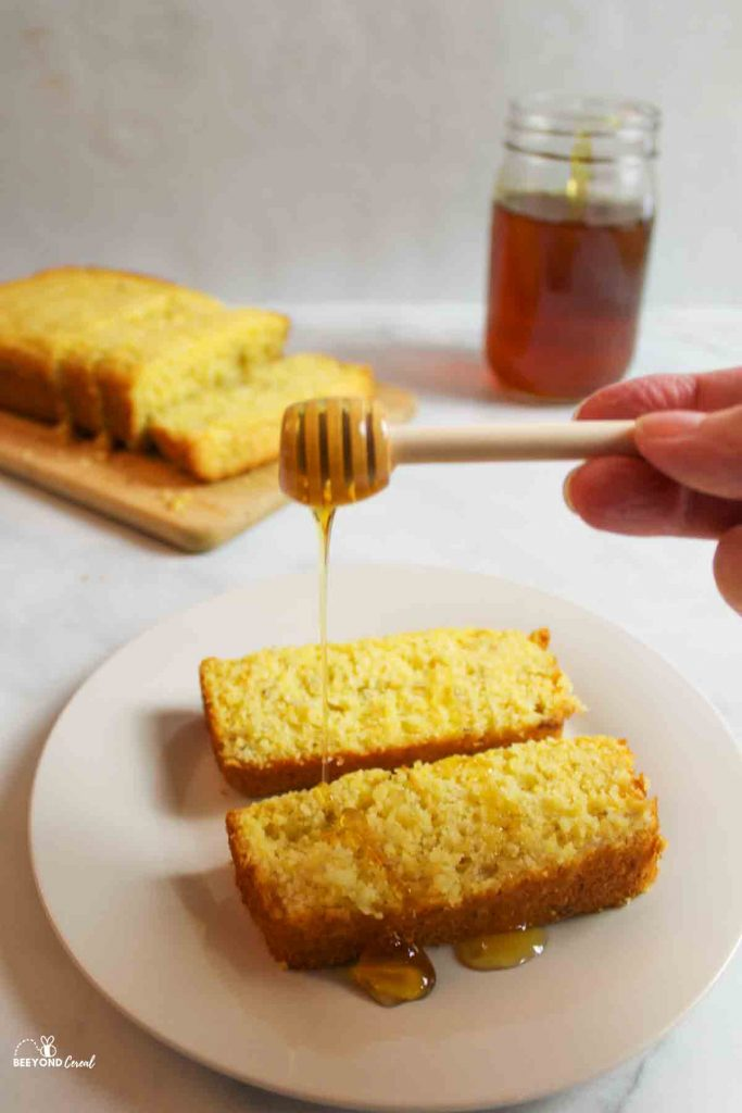 a hand holding a honey stick, drizzling honey over banana cornbread