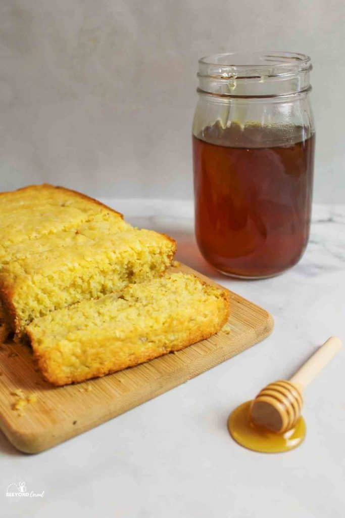 a honey stickto the side of a sliced loaf of banana cornbread and a jar of honey