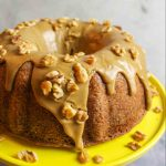 brown sugar glazed banana pound cake on a yellow cake stand with chopped walnuts