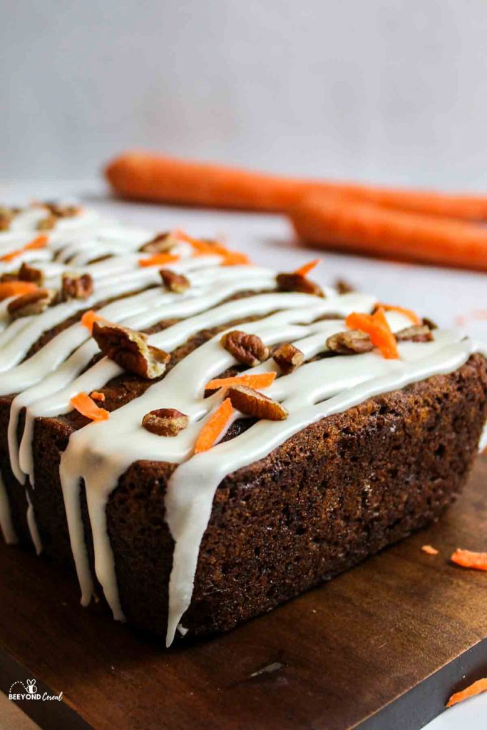an upclose view of a glazed loaf of carrot cake banana bread