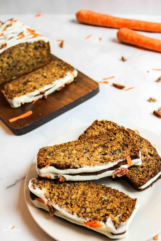 three slices of carrot cake banana bread on a white plate with more on a cutting board to the side