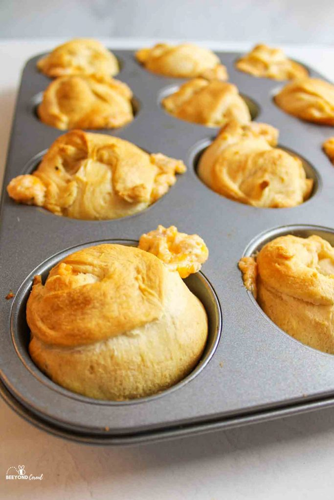 a muffin tray full of baked crescent bombs with some filling spilling out