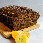 sliced chocolate orange banana bread on a wooden board with fresh fruit slices in front