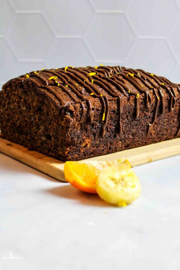 a side view of a glazed chocolate orange banana bread on a wooden board with fresh fruit in front