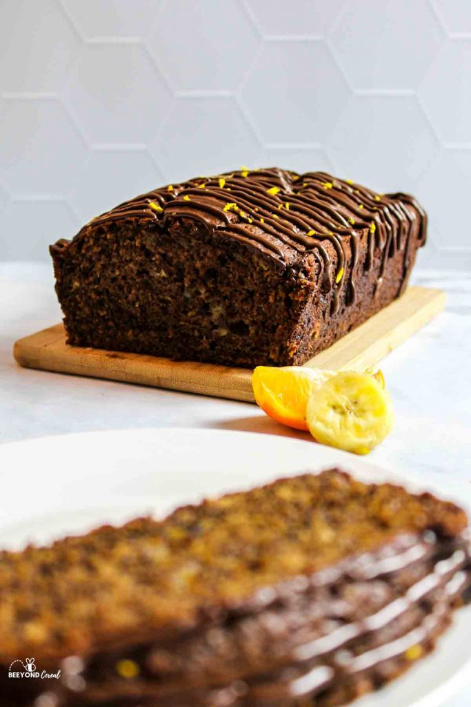 a sliced loaf of chocolate orange banana bread on a wooden board in background with fresh fruit to the side and an out of focus slice in front