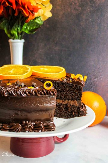 a wedge removed from a slice of orange slice and zest garnished chocolate orange cake
