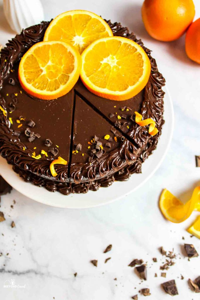 an aerial view of a chocolate orange cake with a slice cut but not removed