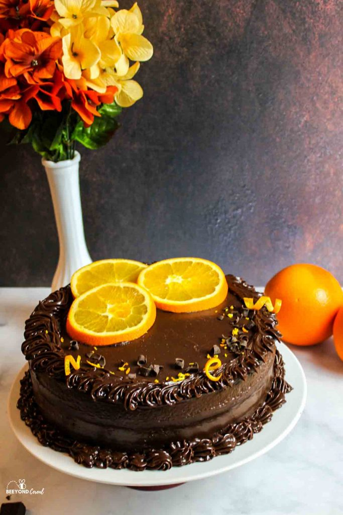 chocolate orange cake on a white plate with orange slices and zest with oranges and flowers in background