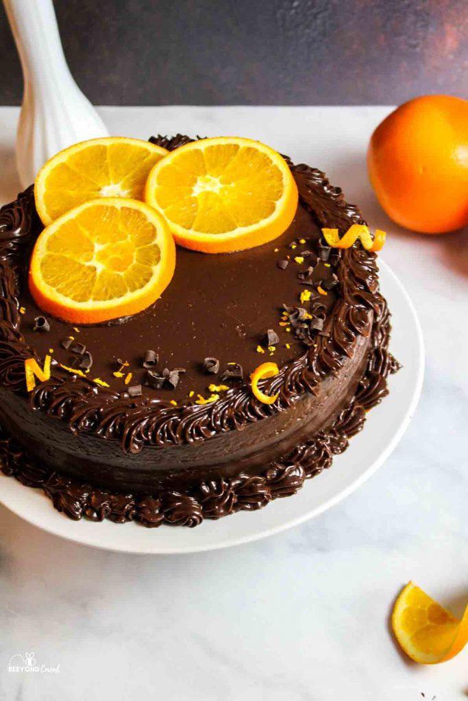 an orange slice and zest garnished chocolate orange cake