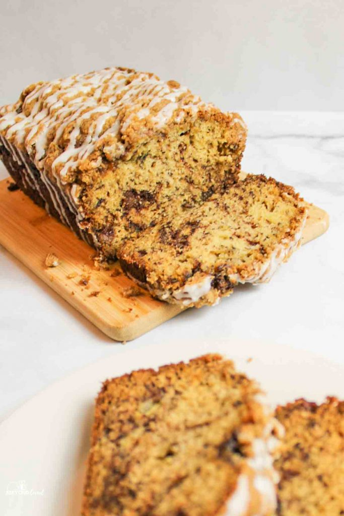 a sliced loaf of Cinnamon Swirl Banana Bread on a cutting board with sliced pieces in front