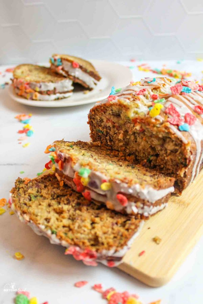 sliced fruity pebbles banana bread on a wooden cutting board with more slices in background