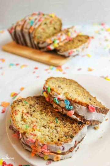 two slices of fruity pebbles banaan bread with a sliced loaf in background