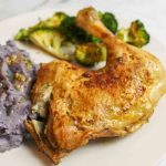 cooked chicken quarter on a plate with purple mashed potatoes and roasted broccoli