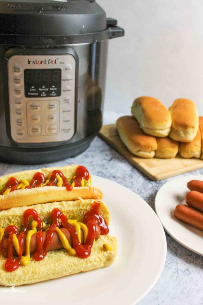 prepared hot dogs on a plate next to cooked hot dogs, buns, and an instant pot