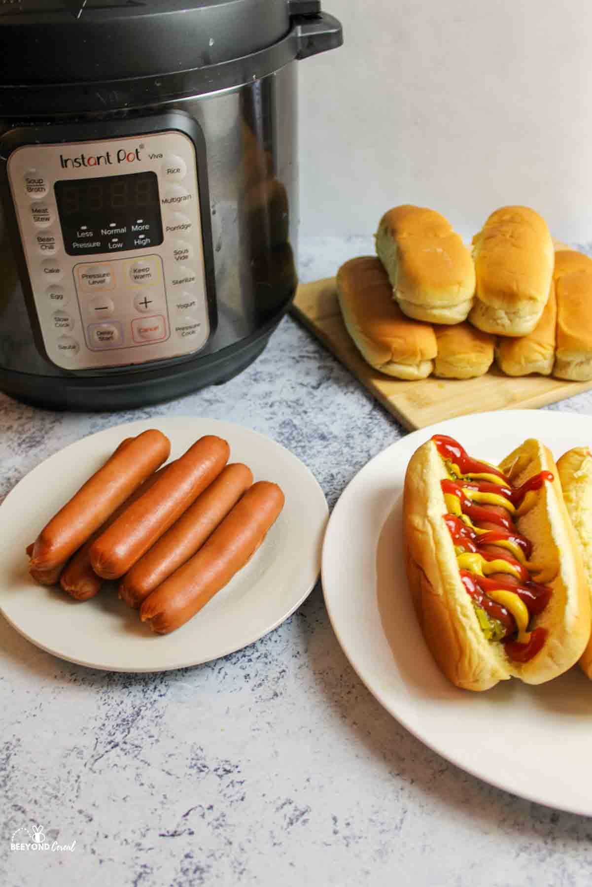 an instant pot next to hot dogs and buns and prepared hot dogs