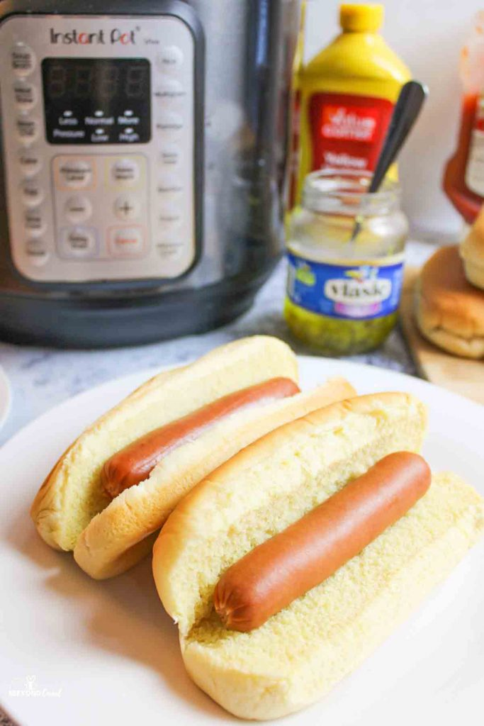 up close view of two cooked hot dogs on buns in front of cindiments and an instant pot