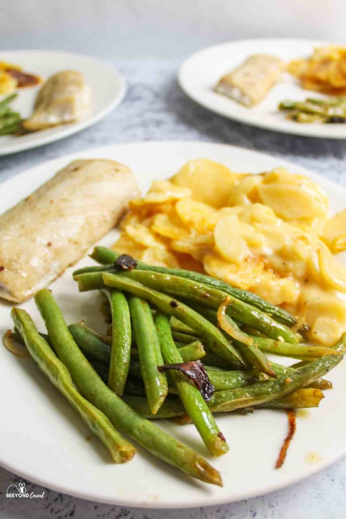 italian green beans on a dinner plate with fish and potatoes