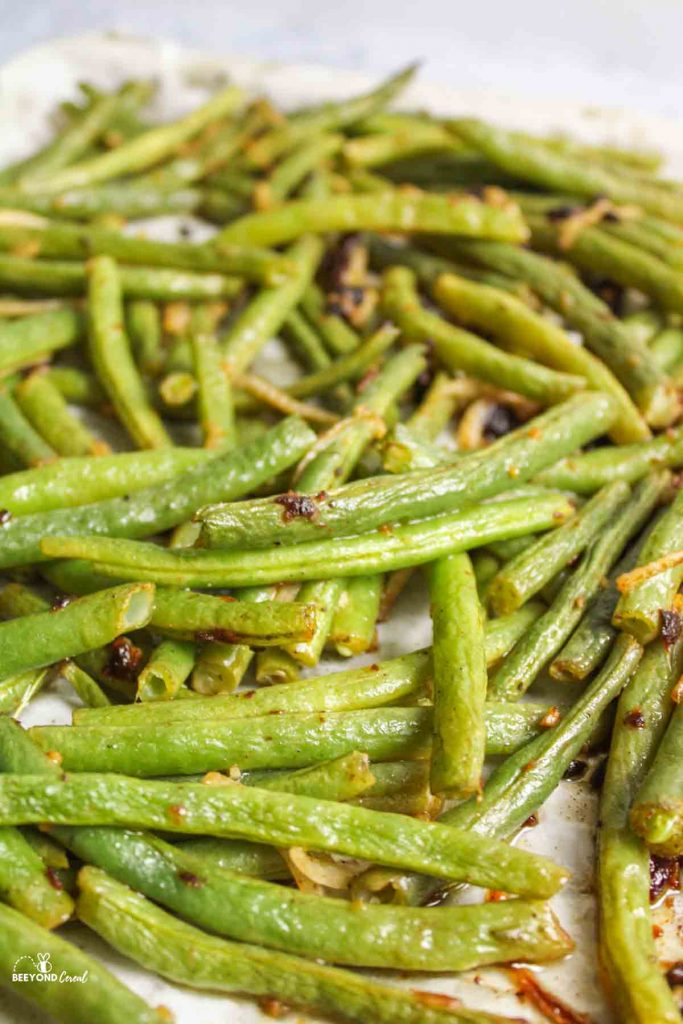 up close view of baked italian green beans on parchment lined baking sheet