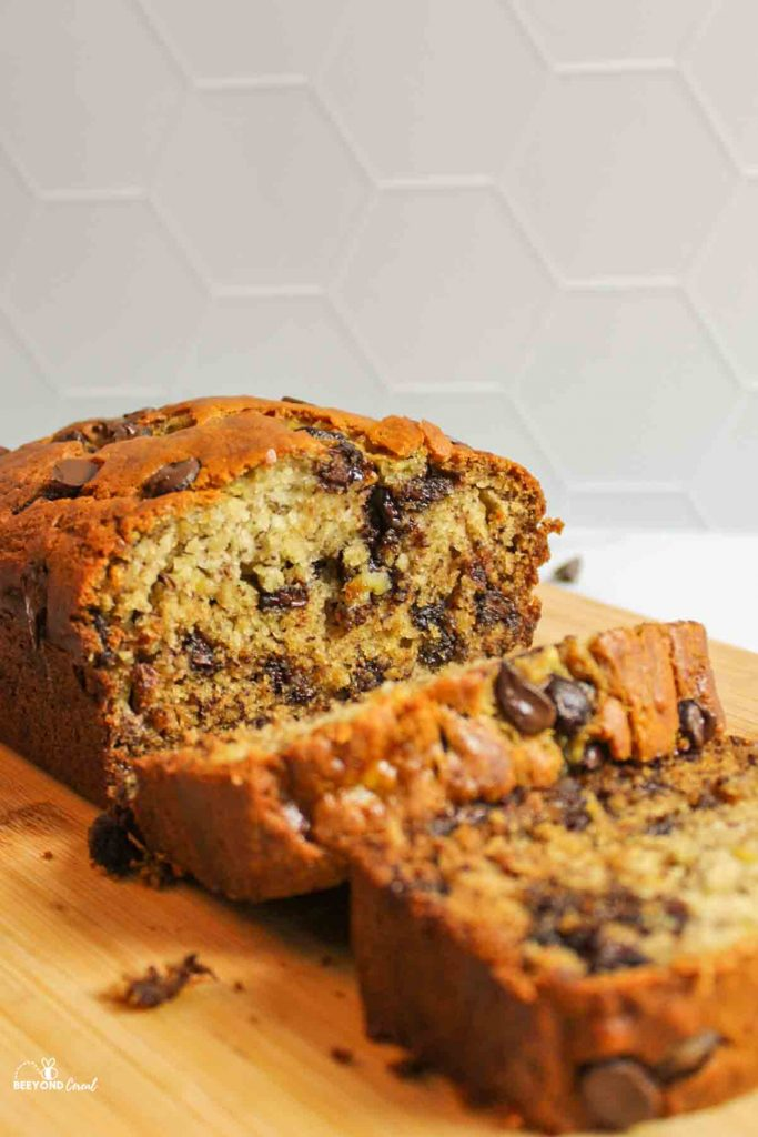 a sliced loaf of chocolate chip banana bread on wooden board showing soft bread crumb texture