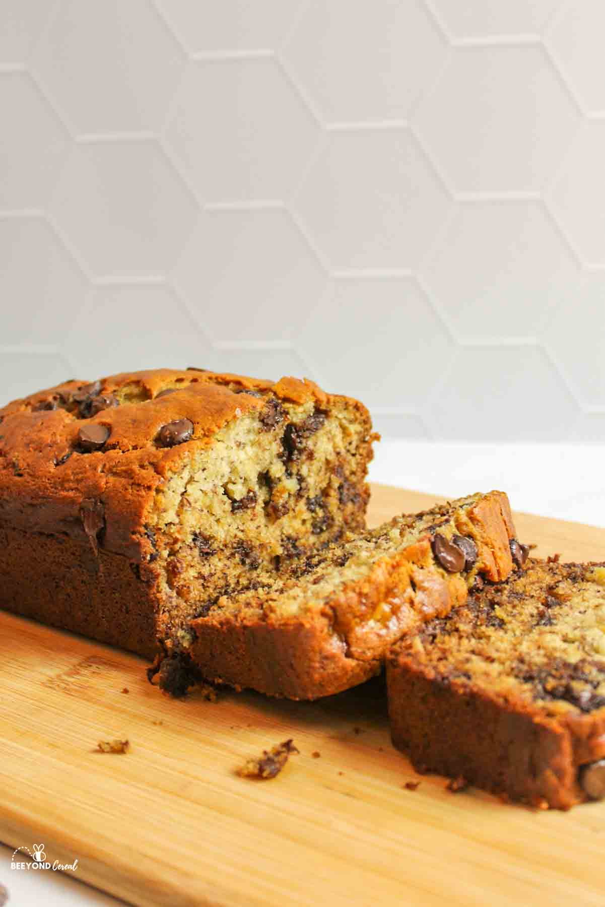 sliced loaf of chocolate chip banana bread on wooden board