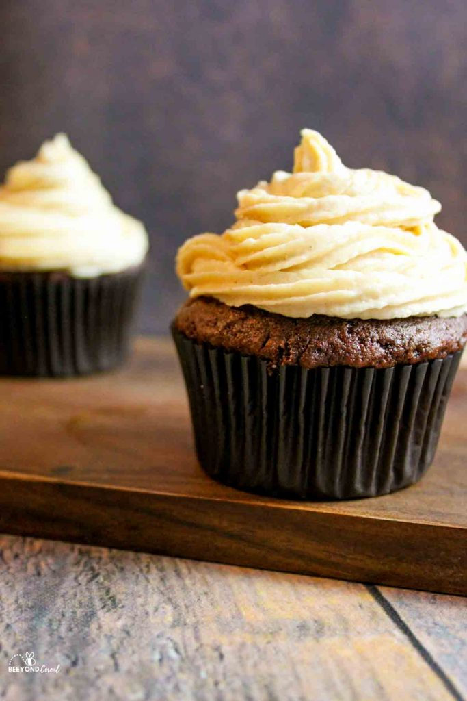 side view of peanut butter cream cheese frosting on a chocolate cupcake with another in the background