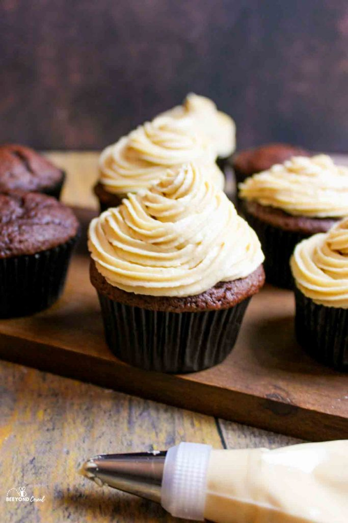 peanut butter cream cheese frosting on chocolate cupcakes and in a piping bag in front